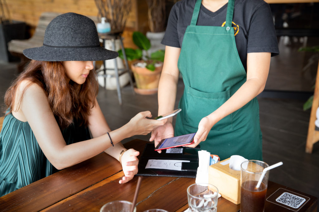 Image of two women using their phones for a bitcoin transaction as a medium of exchange.